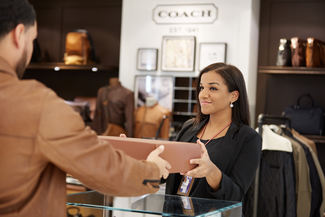 Download Center image link- employee handing over product to a client at coach store